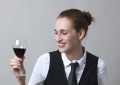 Beautiful young woman wearing uniform of wine waitress looking at aspect and color of red wine
