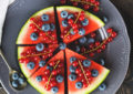 Wedges of watermelon served as pieces of cake with fresh berries on dark rustic background