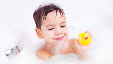 cute four year old boy taking a relaxing bath with foam and playing with a toy duck